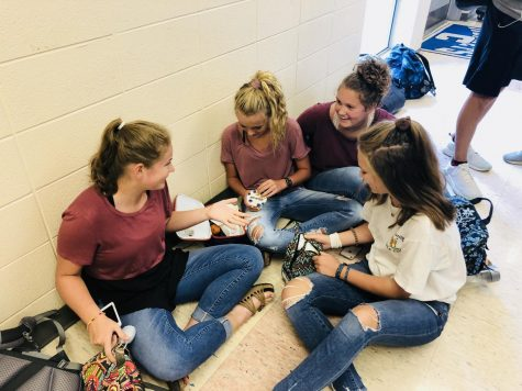 Students, Kathryn Moore, Avery Burleson, Jillian Francis, and Maddie Larkin laugh and talk while eating their lunch in the halls.